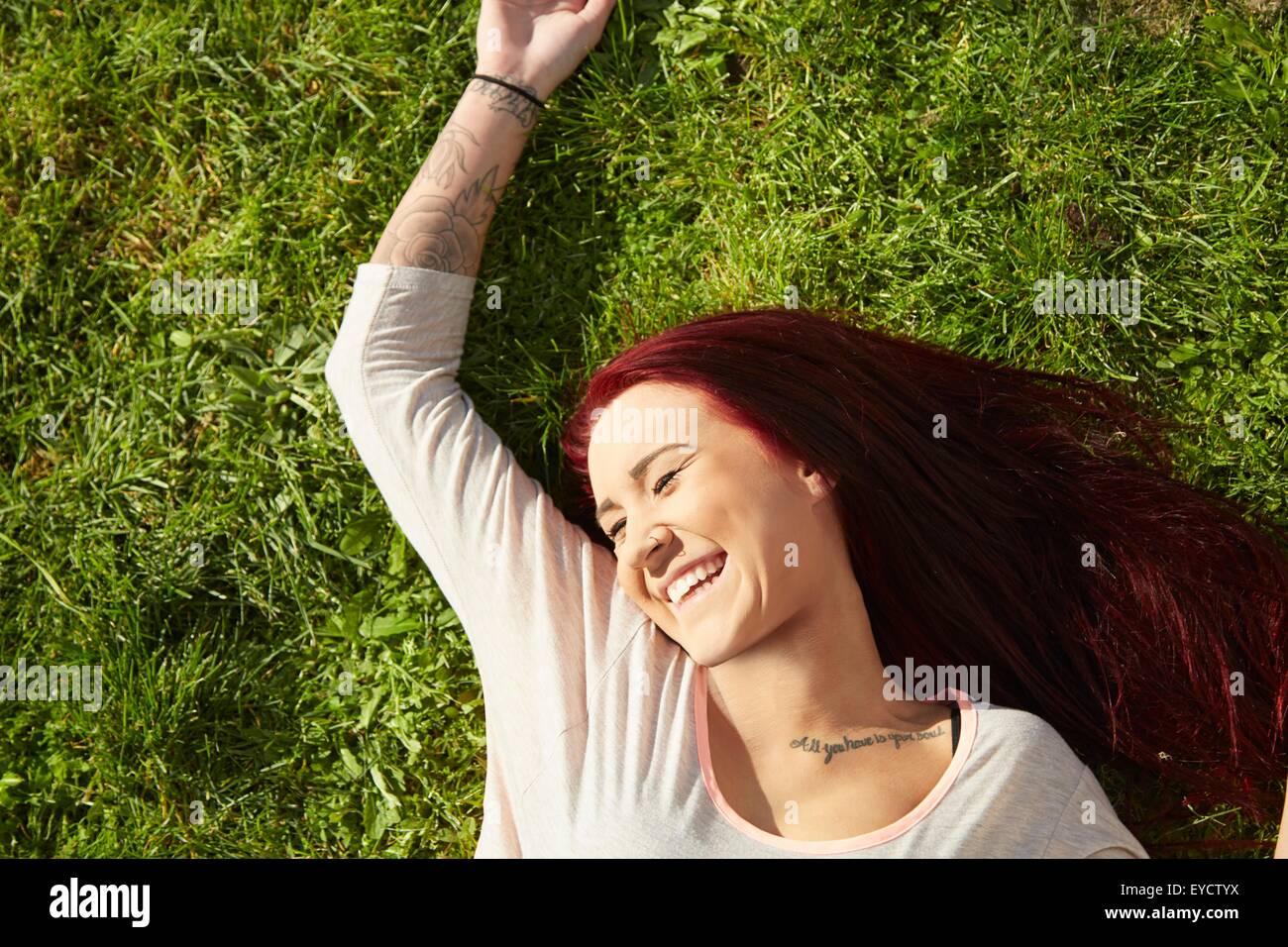 Vista aerea del giovane donna sdraiata su erba ridere Immagini Stock