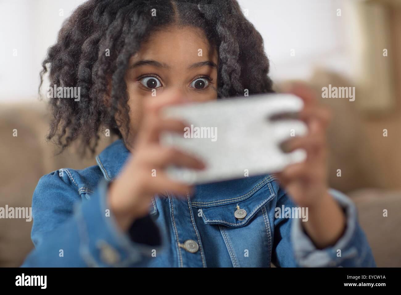 Ravvicinata di una ragazza carina cercando sorpreso per smartphone selfie Immagini Stock