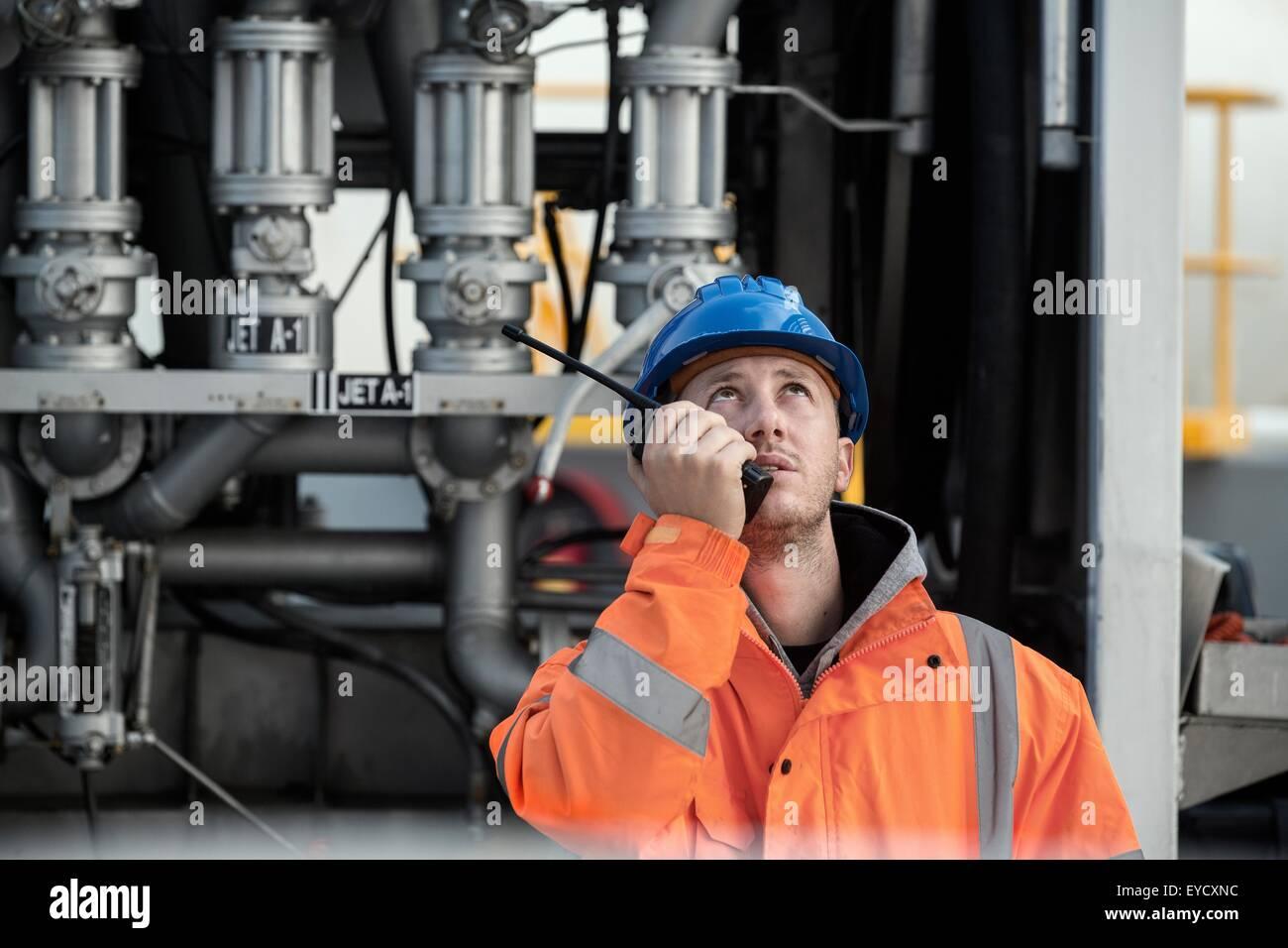 Lavoratore di sesso maschile che parla su radio a due vie a deposito di carburante Immagini Stock