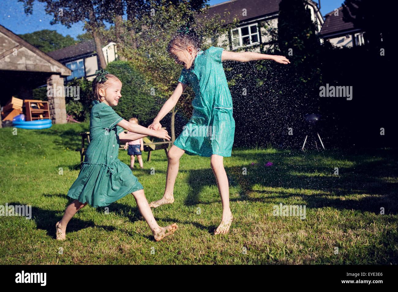 Due bambini nella scuola abiti estivi, in esecuzione attraverso un soffione di erogazione dell'acqua. Immagini Stock
