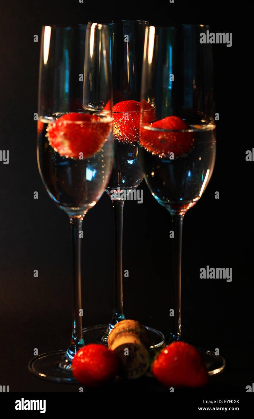 Tre bicchieri di champagne cocktail contro un sfondo nero Immagini Stock