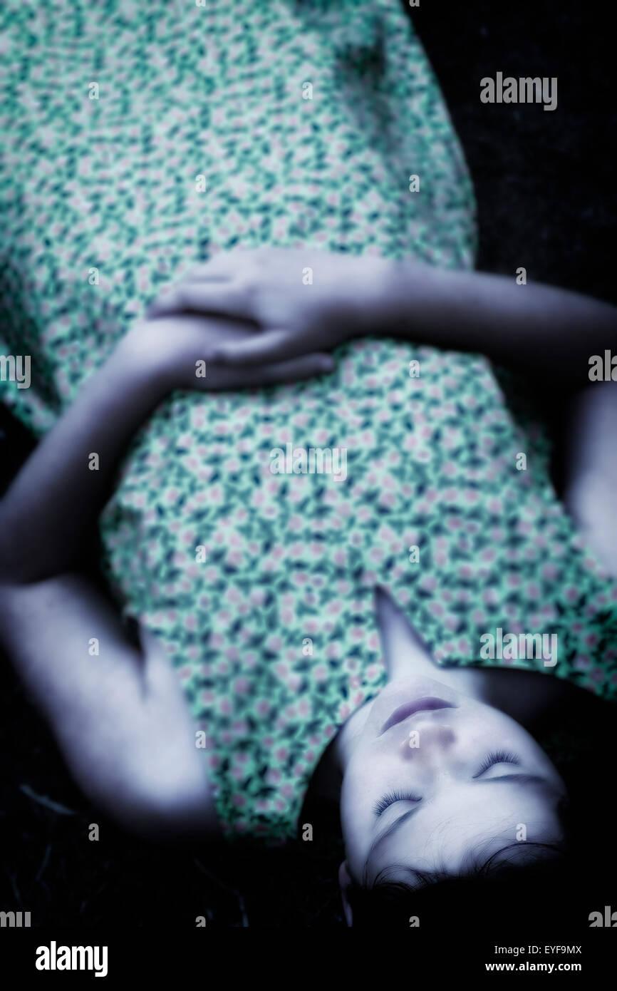 Una ragazza distesa con gli occhi chiusi sul terreno Immagini Stock