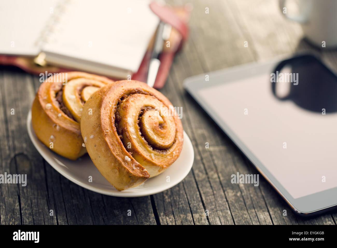 Panini alla cannella, una tazza di caffè e computer tablet. La prima colazione business. Immagini Stock