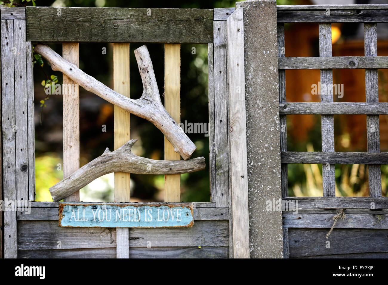 """Un vecchio segno su un cancello di legno che recita """"tutto ciò di cui hai bisogno è l'amore"""" Foto Stock"""