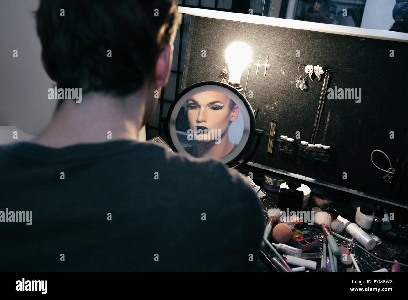 Maschio di drag queen mettendo su make up e vestirsi in preparazione per una performance Foto Stock