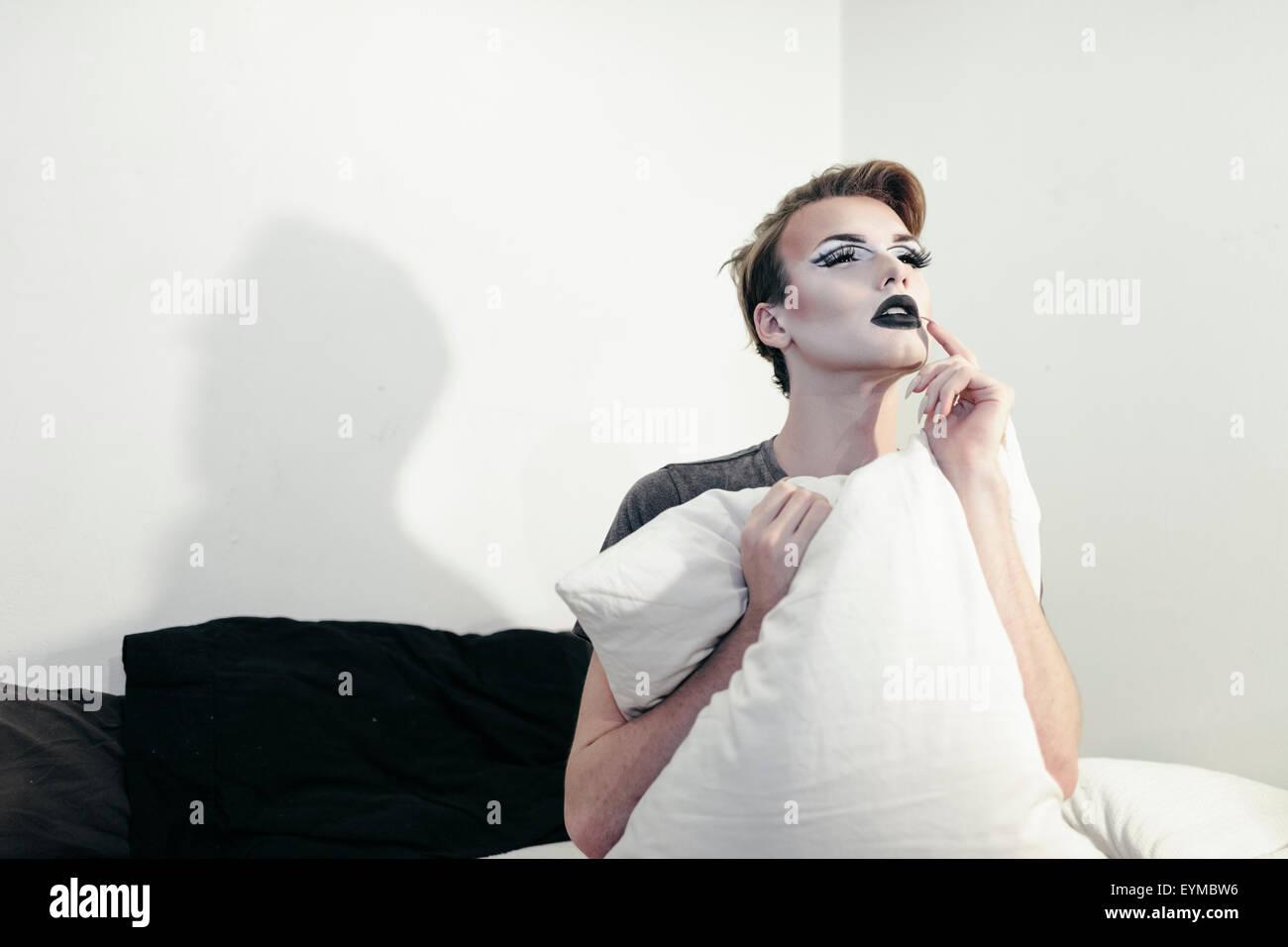Maschio di drag queen in posa per pin-up stile ritratto glamour a casa. Foto Stock