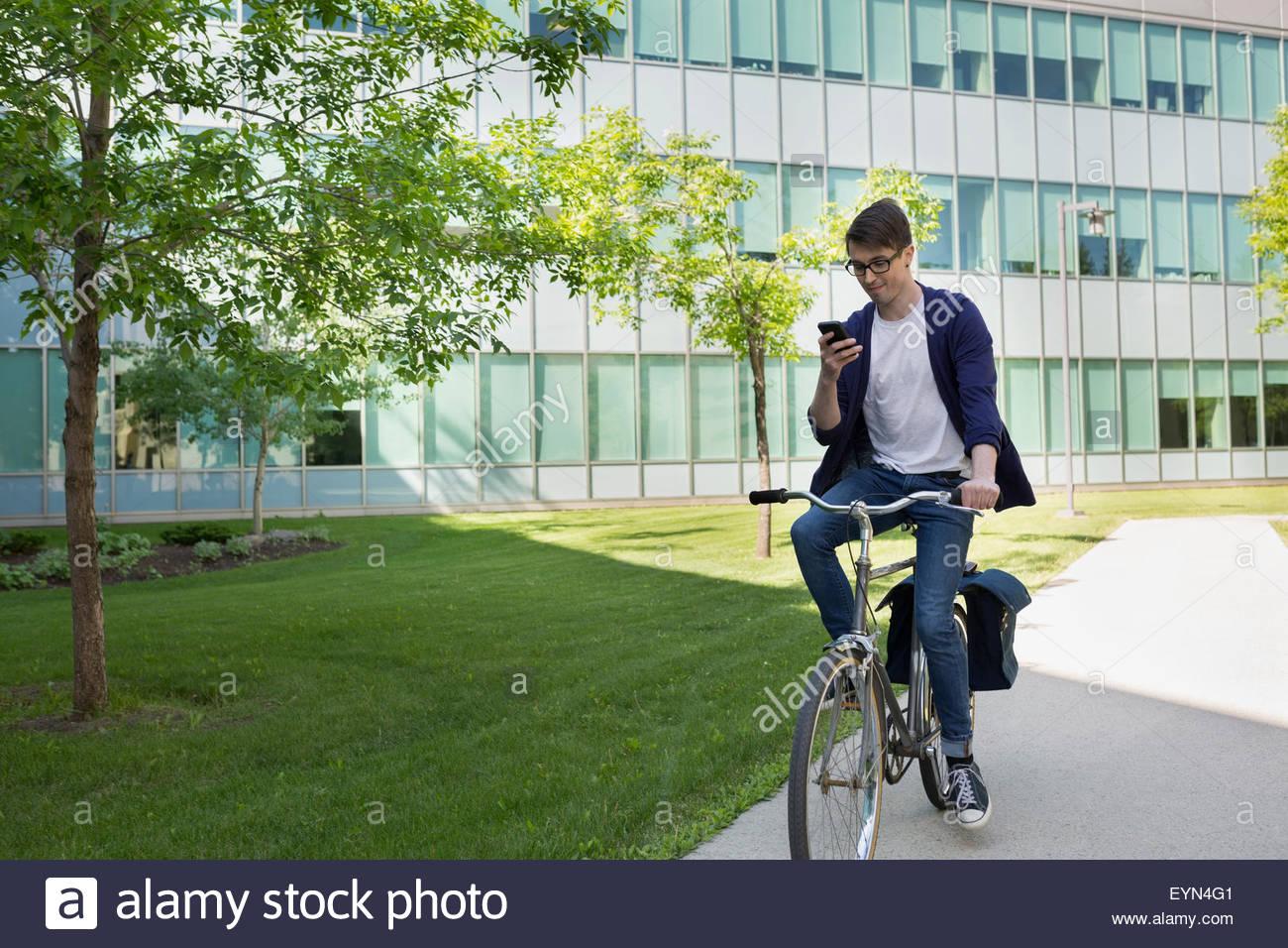 Studente di College in sella bici sul campus e i messaggi di testo Immagini Stock