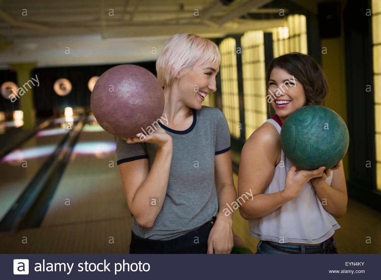 Sorridente giovani donne tenendo le palle da bowling Immagini Stock