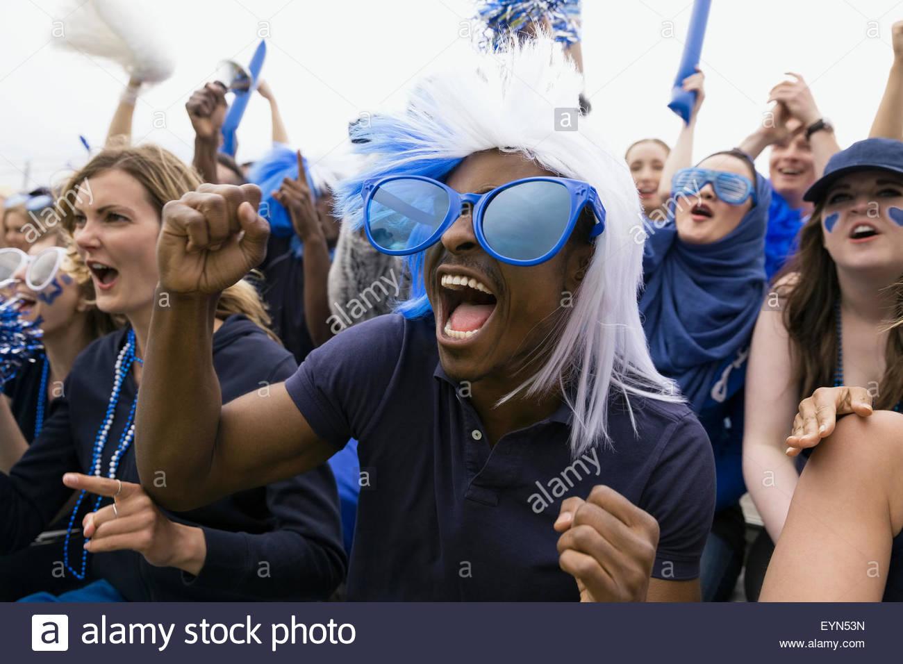 Fan entusiasta nel blu sovradimensionato occhiali da sole il tifo Immagini Stock