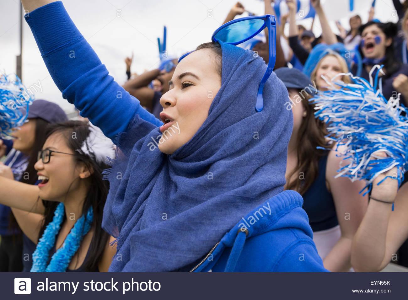 Donna in blu il hijab tifo all evento sportivo Immagini Stock