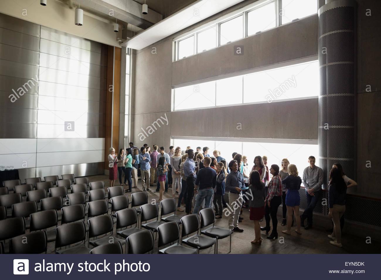 Gli studenti socializzare lungo windows in auditorium Immagini Stock