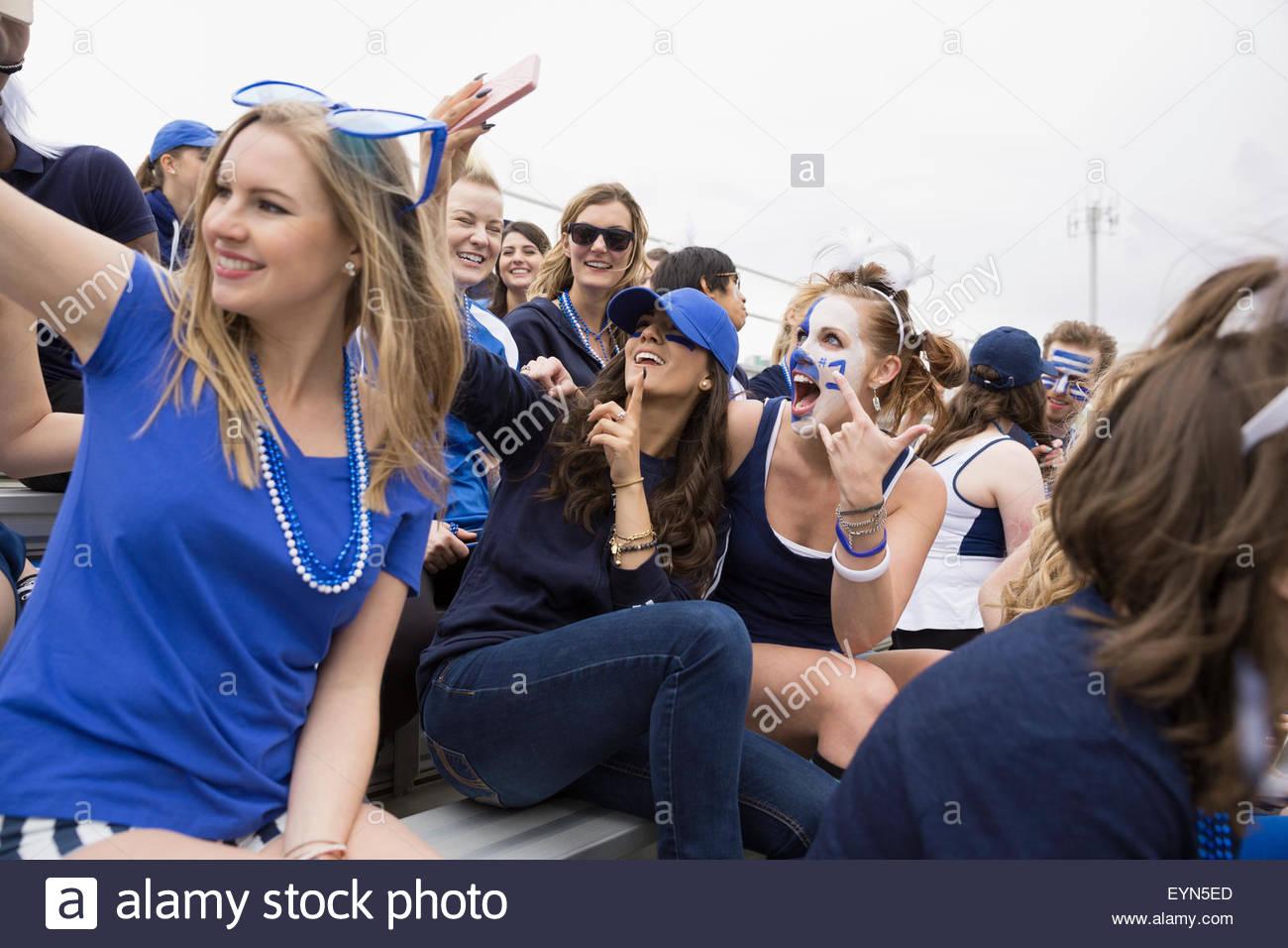 Una platea entusiastica in blu in posa per selfie bleachers Immagini Stock