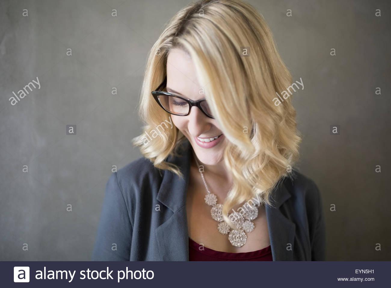 Ritratto sorridente imprenditrice biondo con gli occhiali guardando verso il basso Immagini Stock