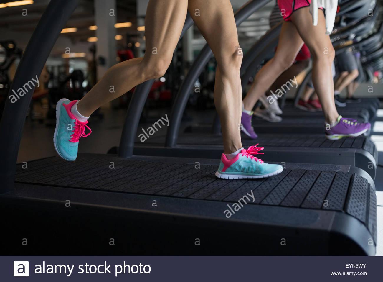 Le gambe delle donne in esecuzione sul tapis roulant in palestra Immagini Stock