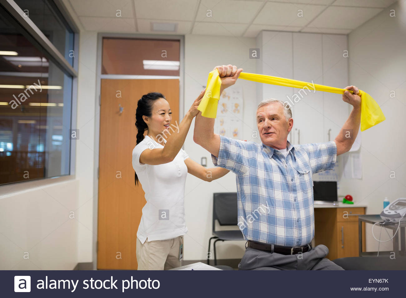 Fisioterapista paziente guida con banda di resistenza Immagini Stock