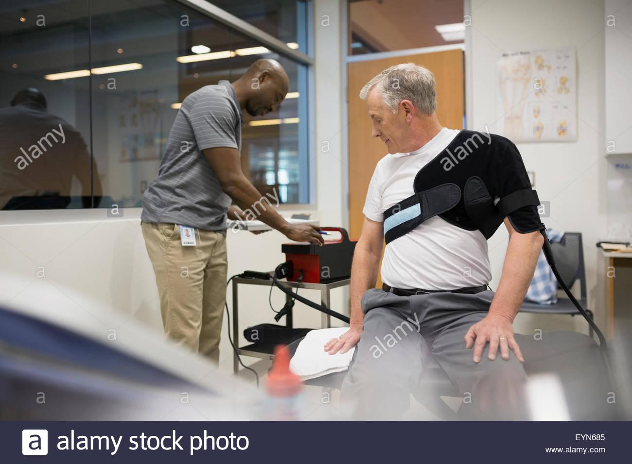 Terapista fisico usando la spalla avvolgere su paziente Immagini Stock
