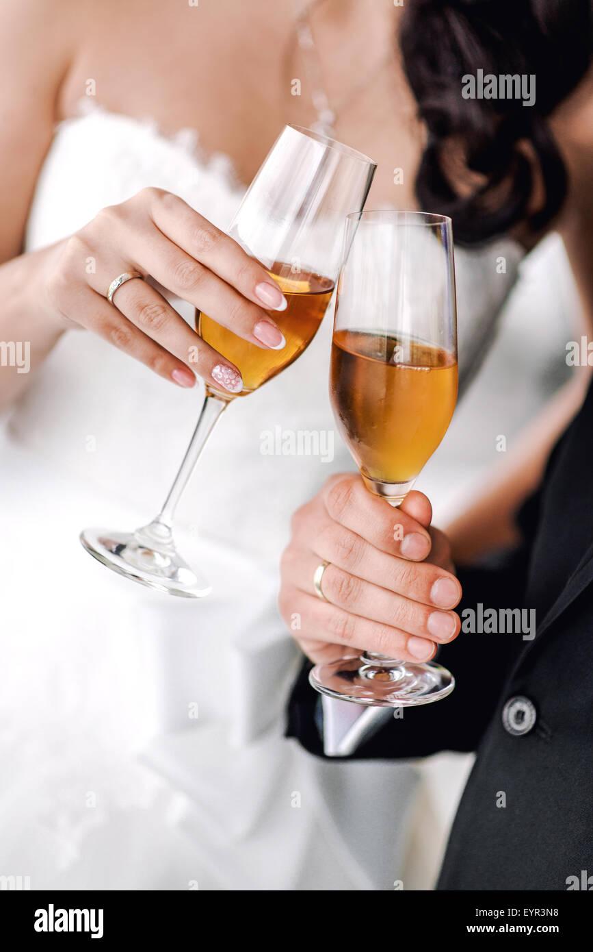 Le mani della sposa e lo sposo con bicchieri di champagne Immagini Stock