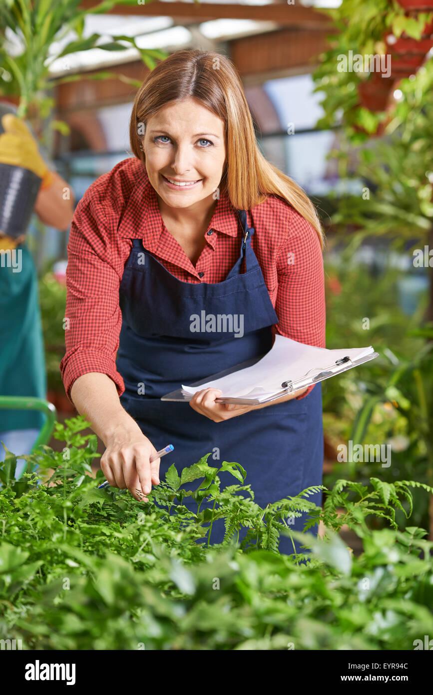 Giardiniere con appunti in giardino centro controllo la crescita di piante Immagini Stock