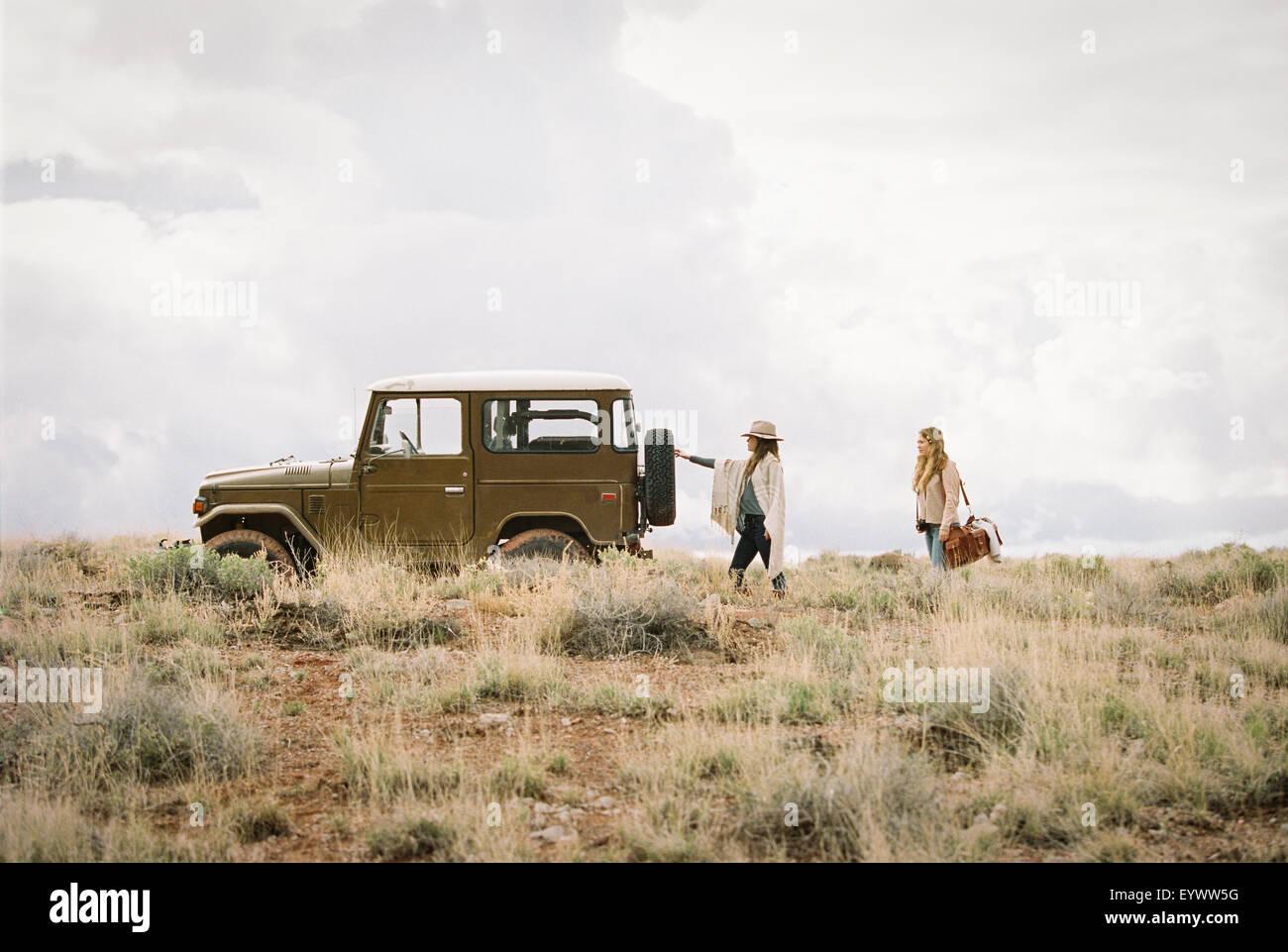 Due donne con una jeep in spazio aperto, il caricamento per un viaggio su strada. Immagini Stock