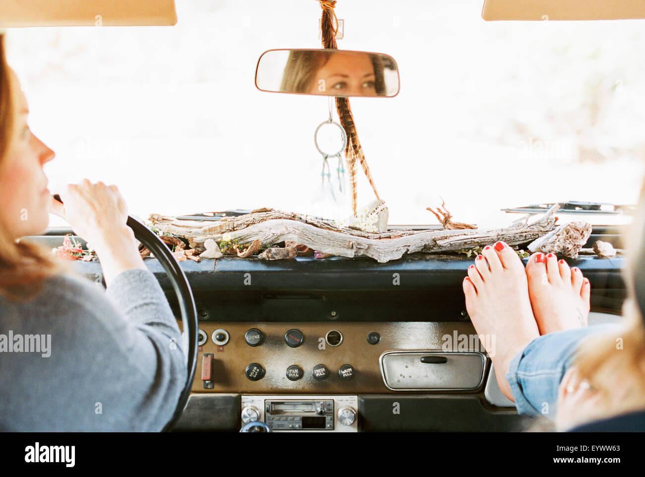 Una donna in appoggio il suo piedi nudi sul cruscotto di un 4x4, un viaggio con un'altra donna alla guida. Immagini Stock
