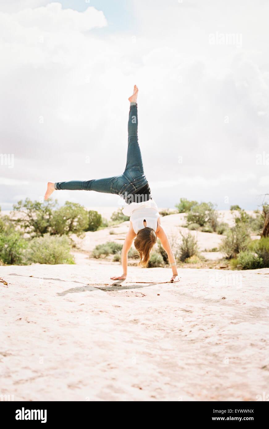 A piedi nudi donna che indossa jeans, cartwheeling Immagini Stock