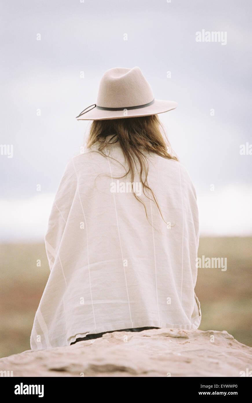 Vista posteriore di una donna che indossa un cappello e wrap caldi Immagini Stock