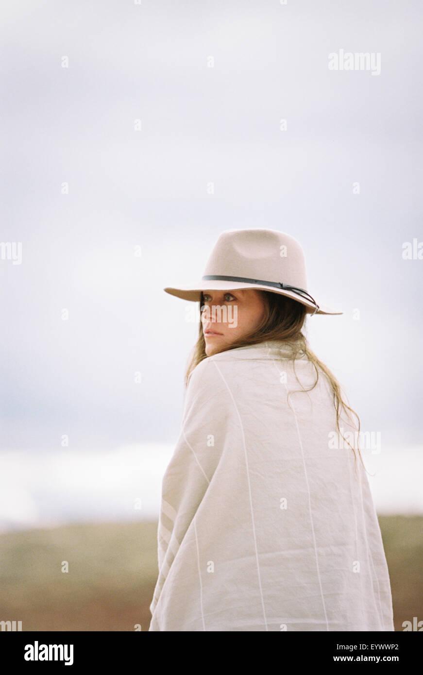 Donna che indossa un cappello e avvolgere sorridente alla fotocamera. Immagini Stock