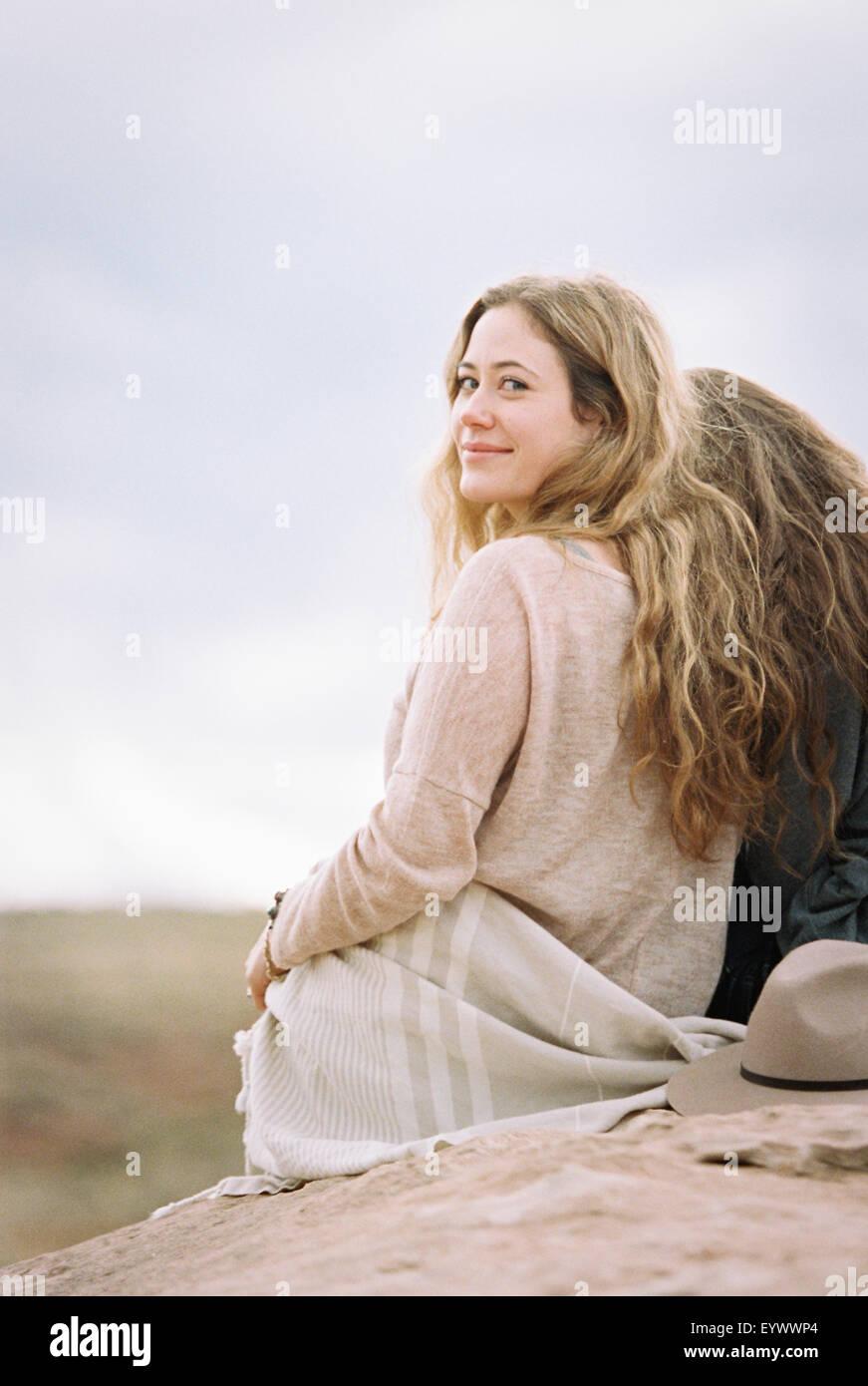 Due donne uno guardando sopra la sua spalla, sorridente Immagini Stock
