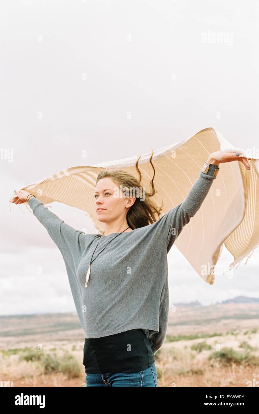 Donna che mantiene un wrap che fluttua nel vento. Immagini Stock