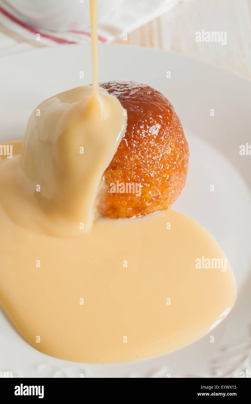Vaporizzato sciroppo dorato budino di spugna e la crema alla vaniglia Immagini Stock