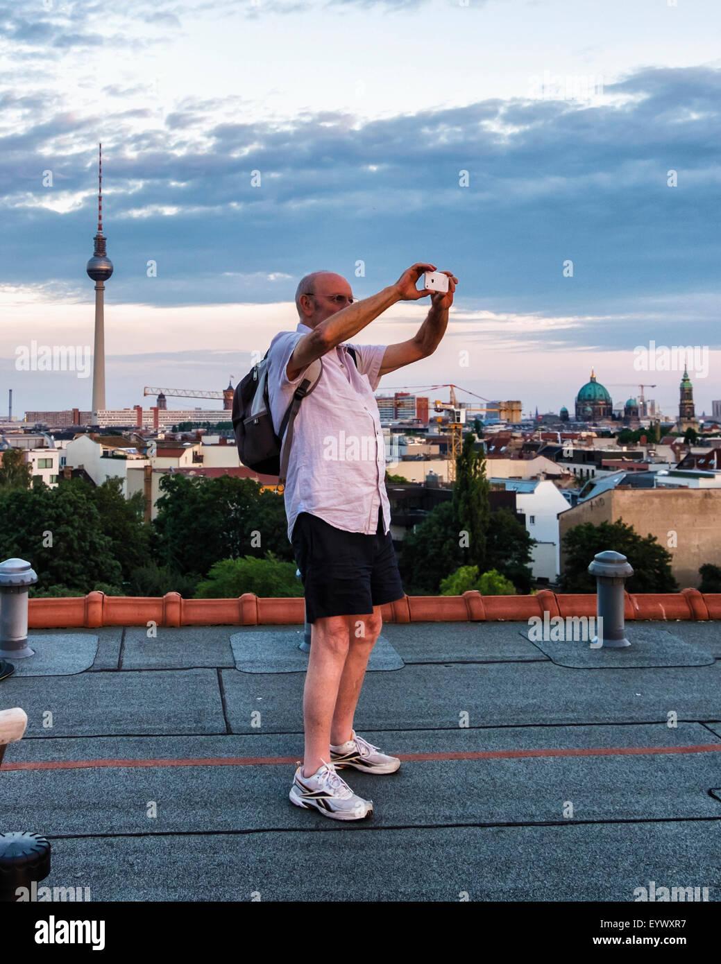 Senior l uomo si prende la fotografia sul I-phone di Berlino skyline vista dall'appartamento attico al tramonto Immagini Stock