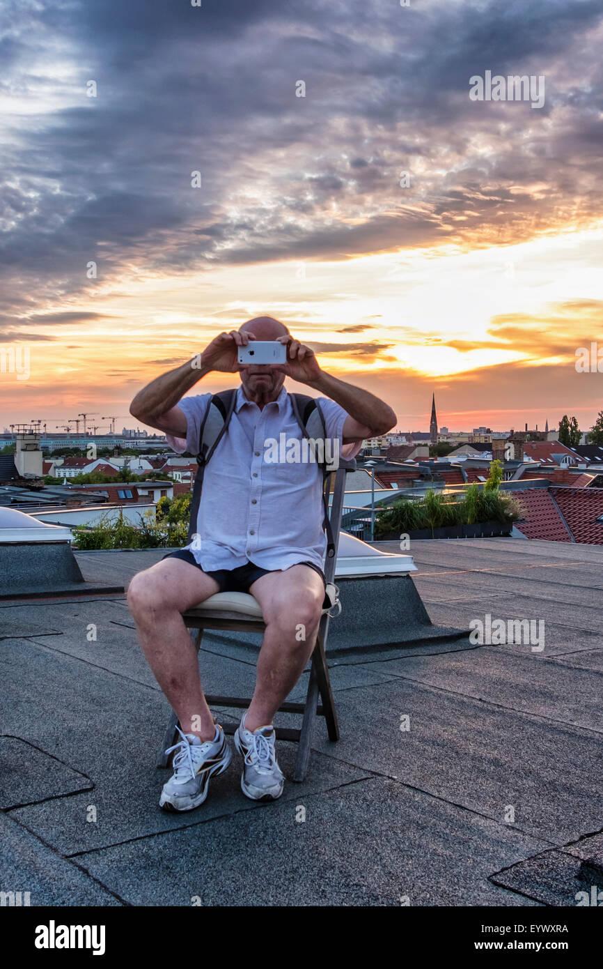 Senior l uomo si prende la fotografia sul I-phone di Berlino vista dall'appartamento attico al tramonto Immagini Stock