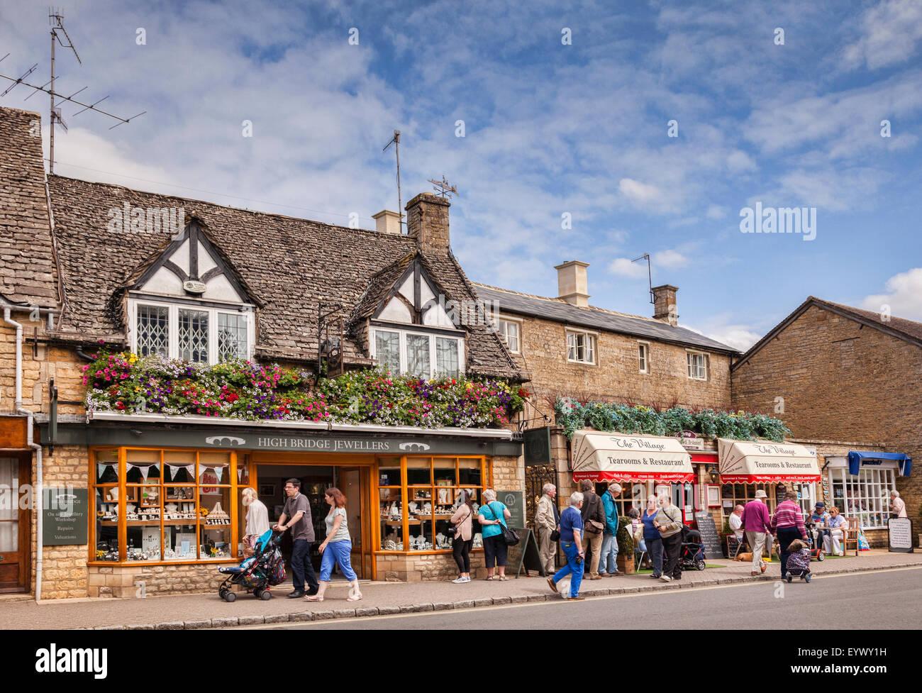 I turisti in High Street a Bourton-on-the-acqua, Gloucestershire, Inghilterra. Immagini Stock