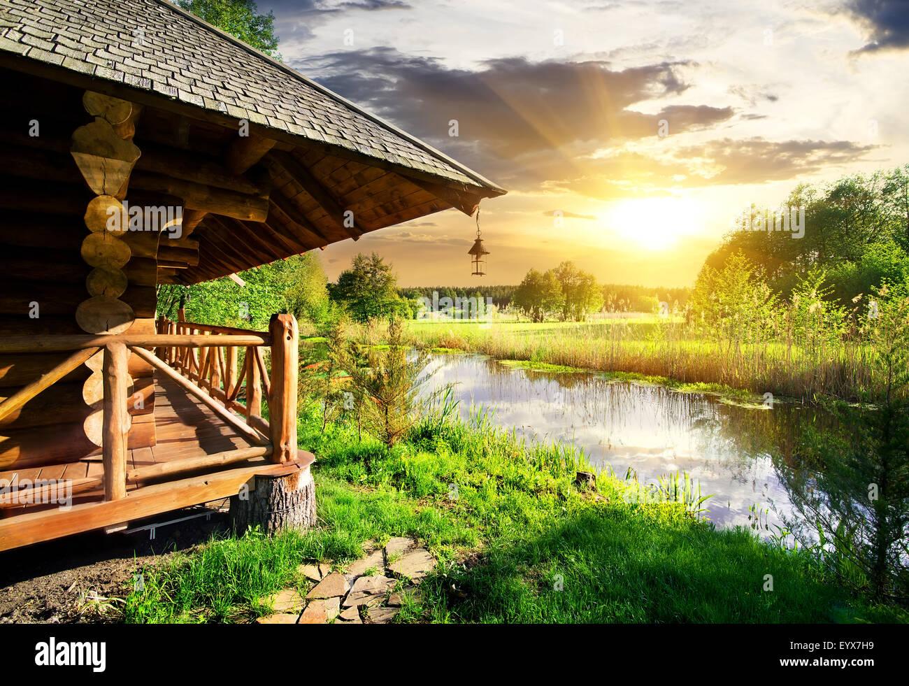 Capanno di legno vicino al lago al tramonto Immagini Stock