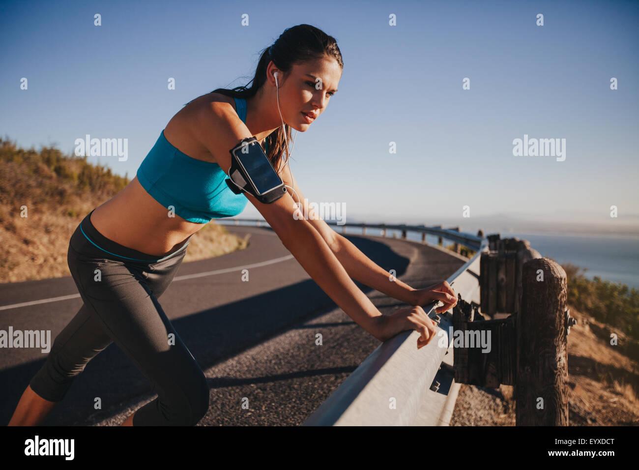 Giovane atleta femminile poggiando su autostrada guardrail guardando lontano. Donna runner fuori sulla strada di Immagini Stock