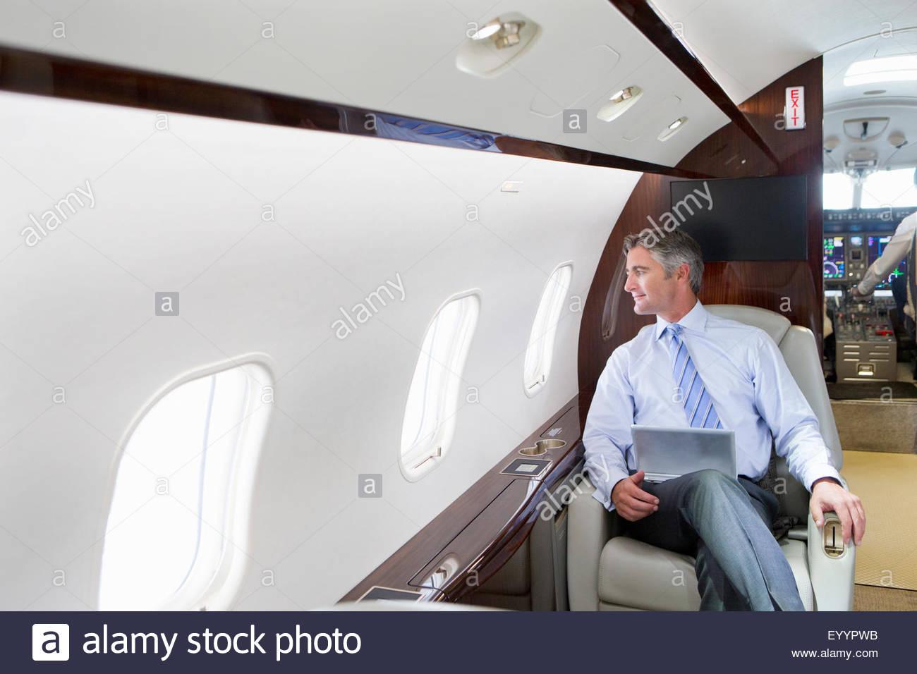 Imprenditore con tavoletta digitale guardando fuori della finestra sul jet privato Immagini Stock