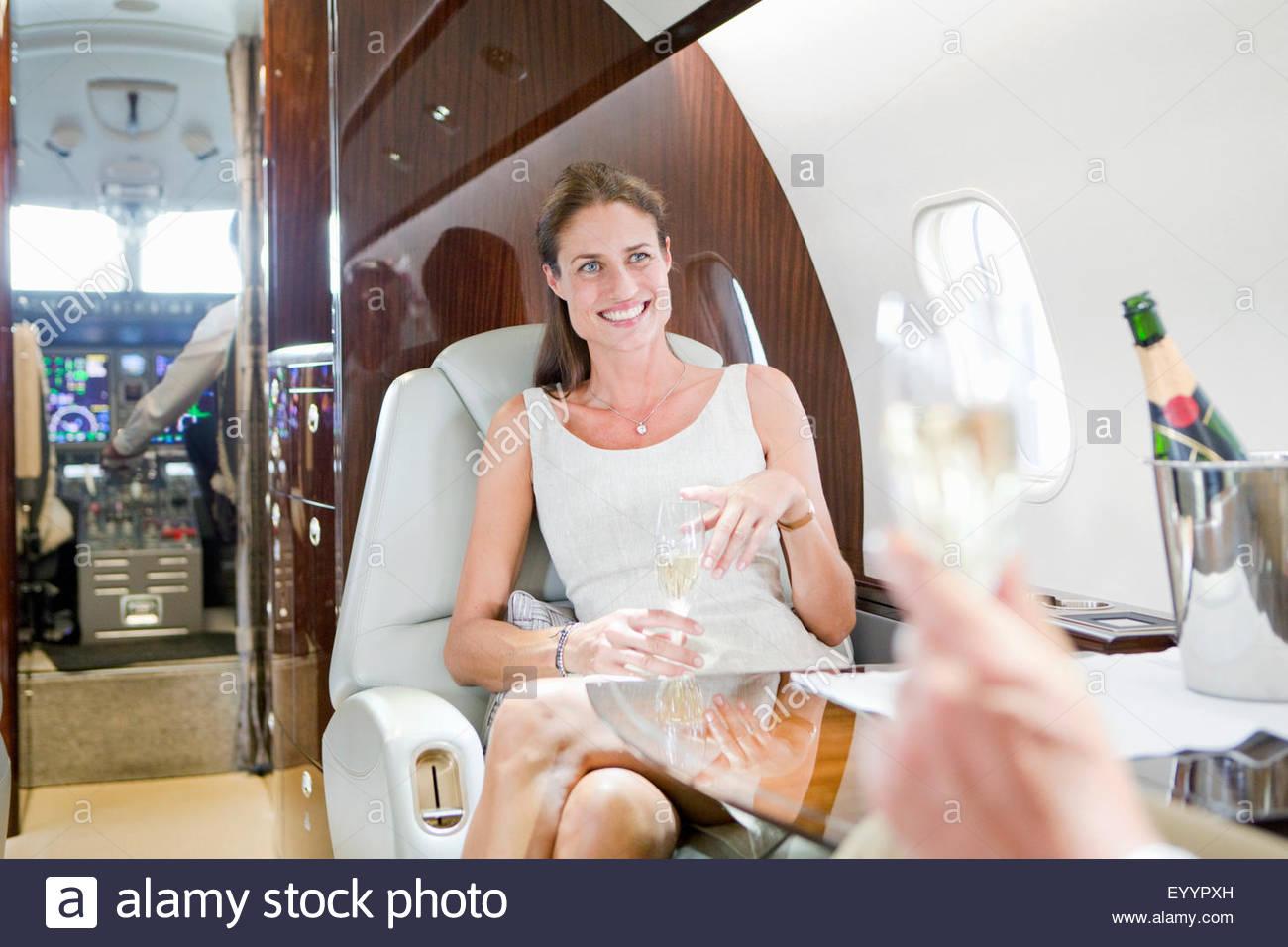 Attraente donna sorridente bevendo champagne sul jet privato Immagini Stock