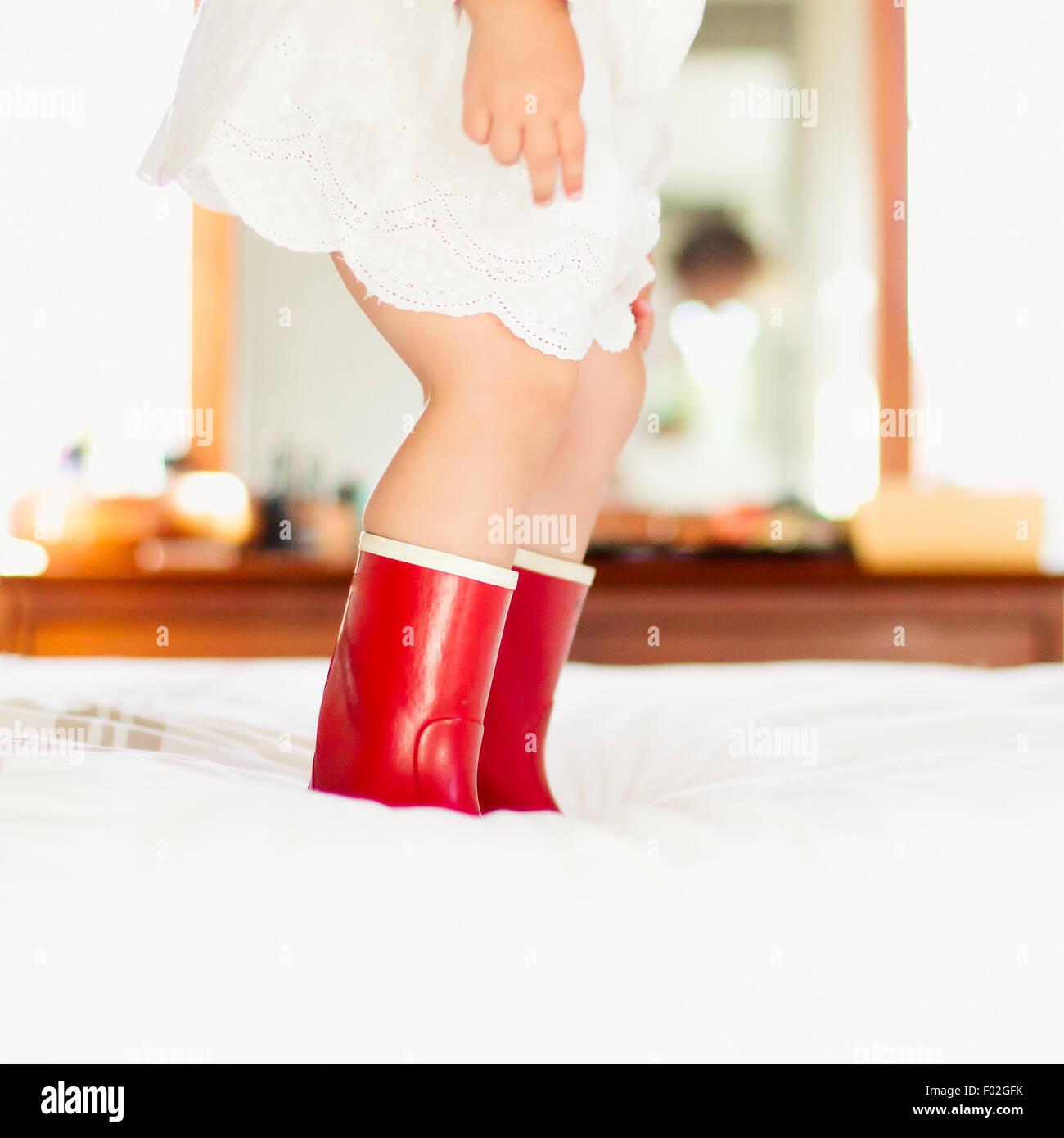 Close-up di una ragazza in stivali rossi saltando su un letto Immagini Stock