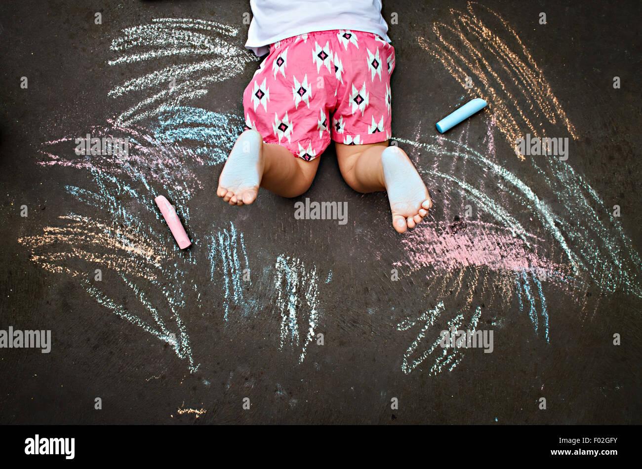Vista aerea della ragazza distesa a terra il disegno con Chalk Immagini Stock