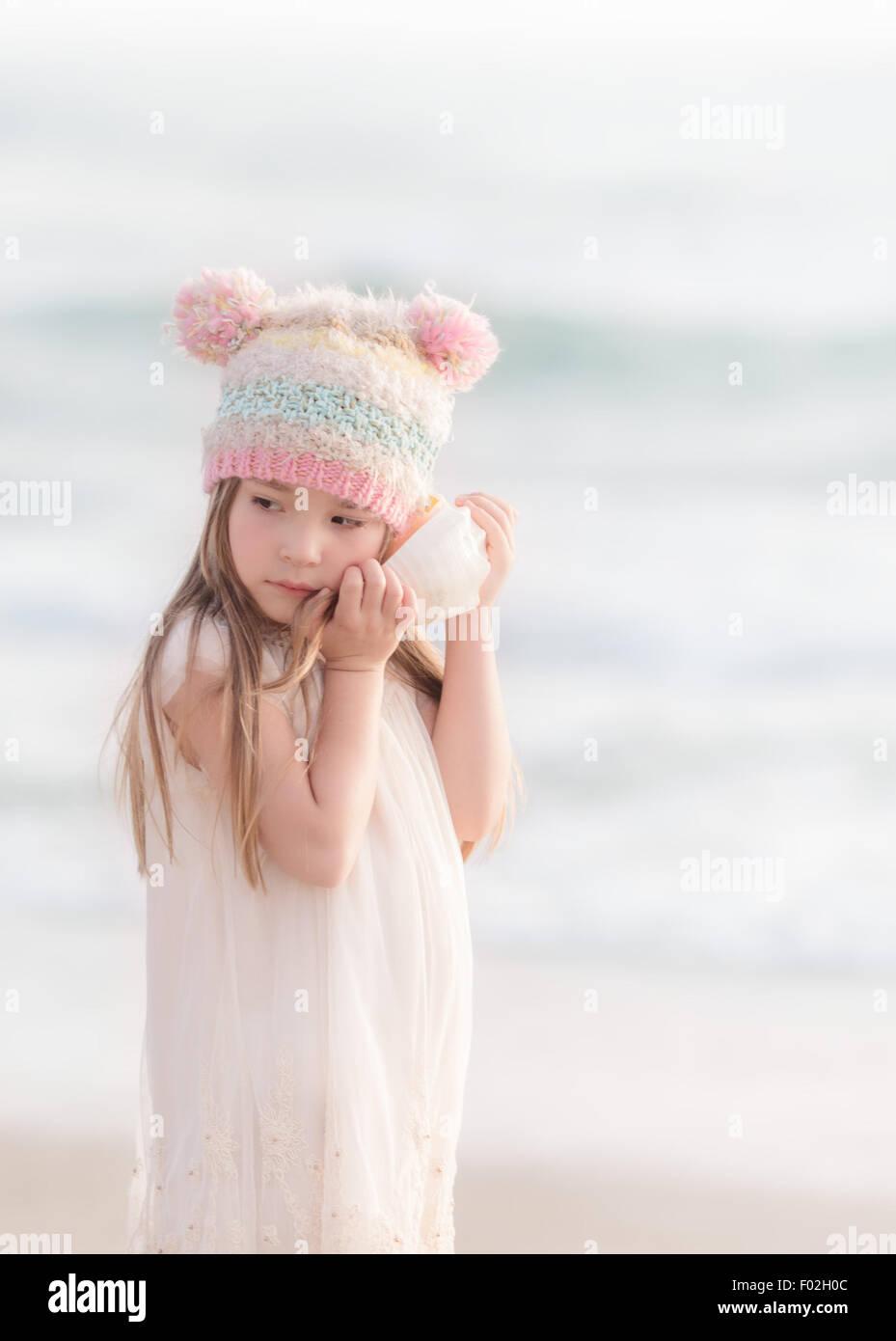 Ragazza in piedi sulla spiaggia ascoltando una conchiglia Immagini Stock