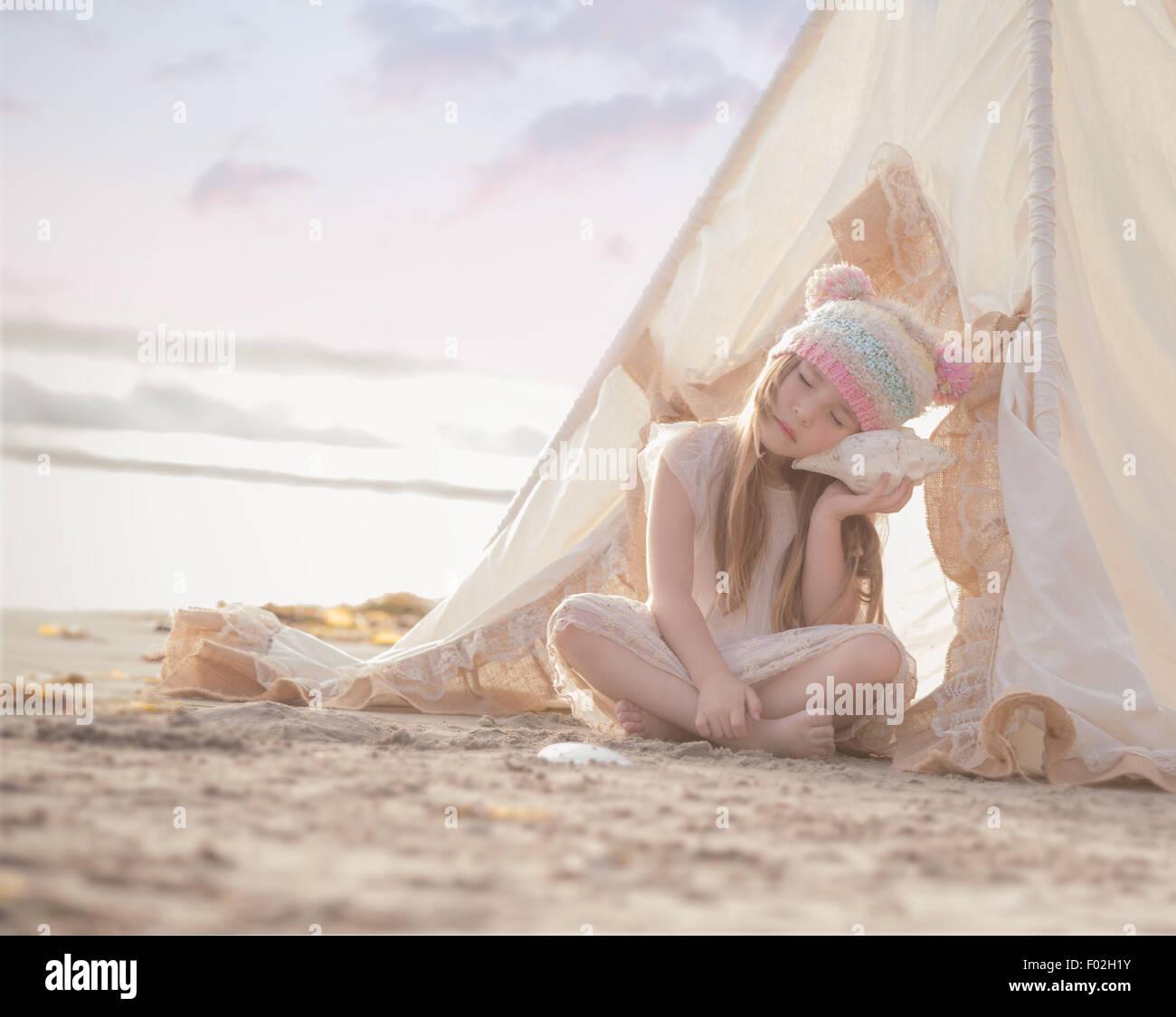 Ragazza seduta in un wigwam sulla spiaggia ascoltando una conchiglia Immagini Stock