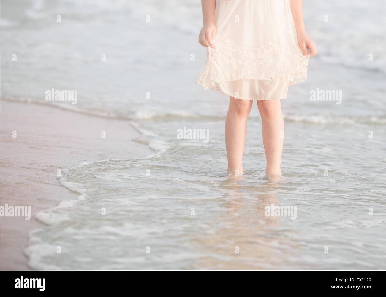 Ragazza in piedi il surf in spiaggia Immagini Stock