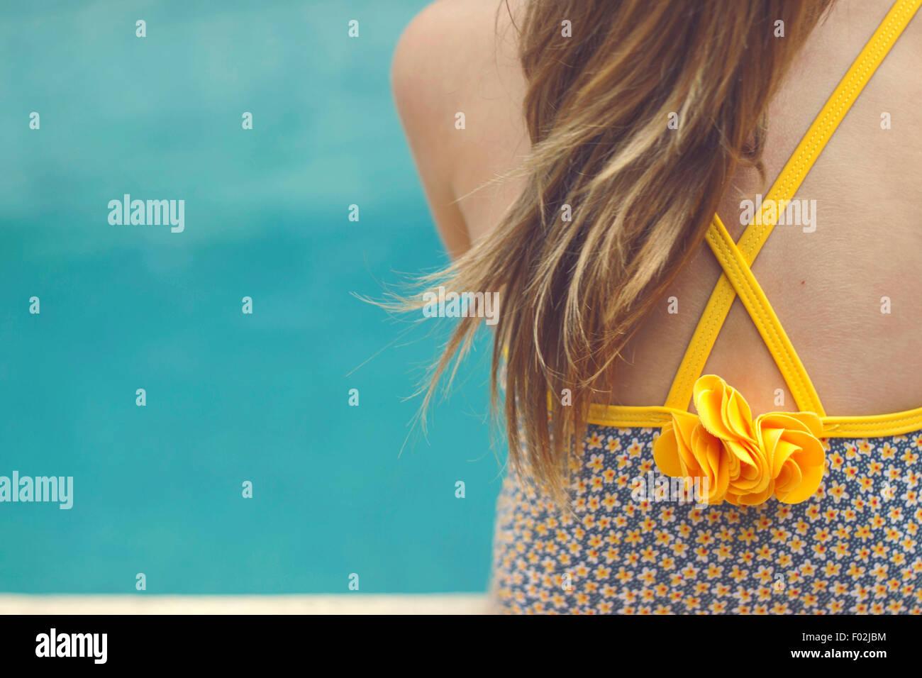 Vista posteriore di una ragazza in un costume da bagno seduta da una piscina Immagini Stock