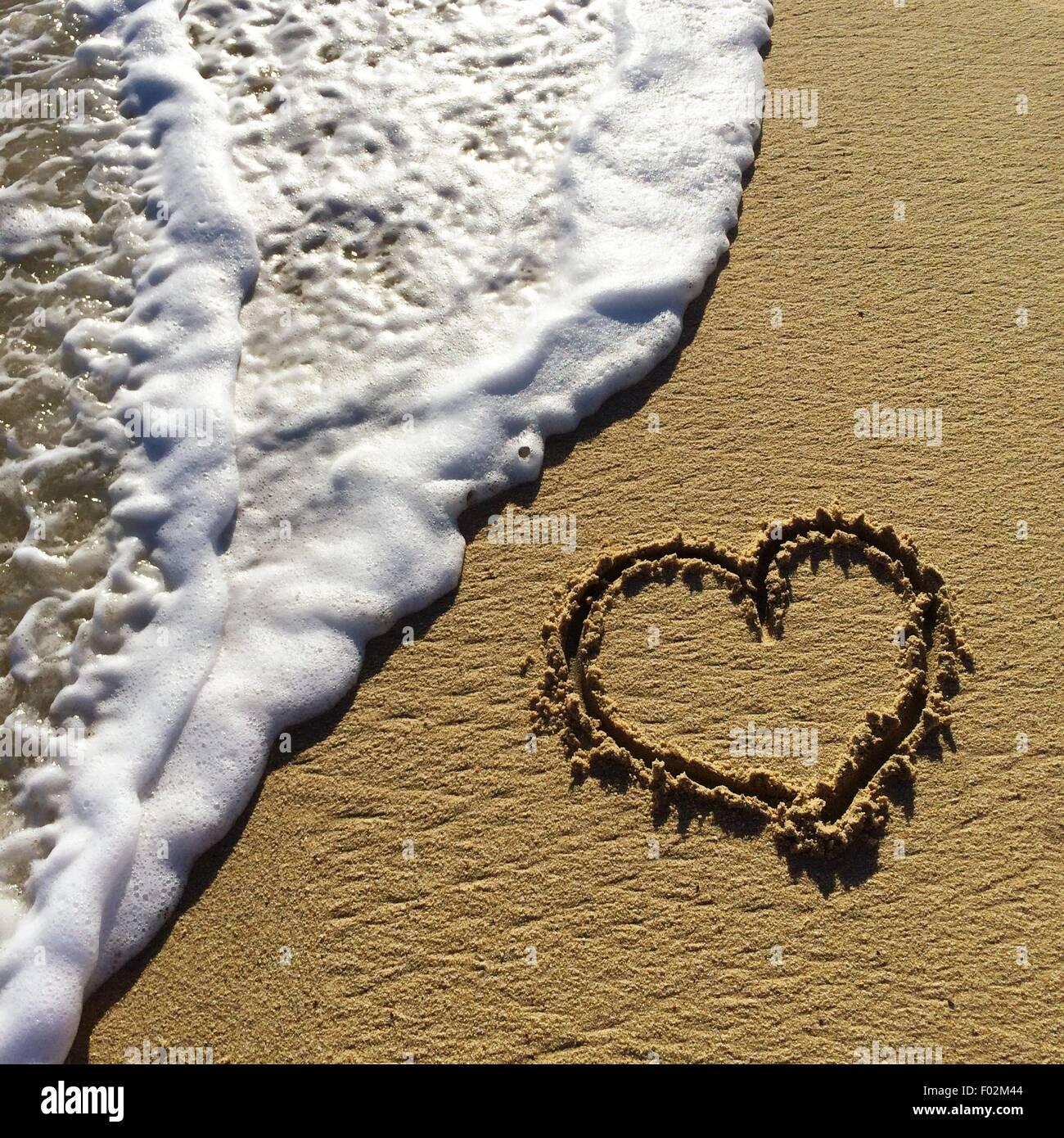 Forma di cuore disegnato nella sabbia sulla spiaggia Immagini Stock