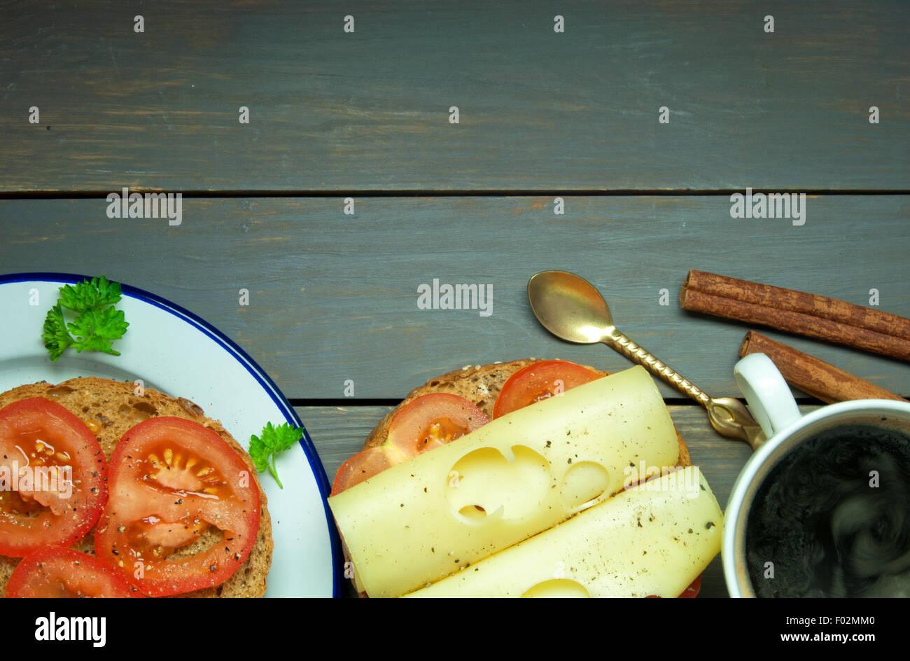 Formaggio e sandwich di pomodoro con una tazza di caffè sulla parte superiore di una tavola di legno con spazio Immagini Stock