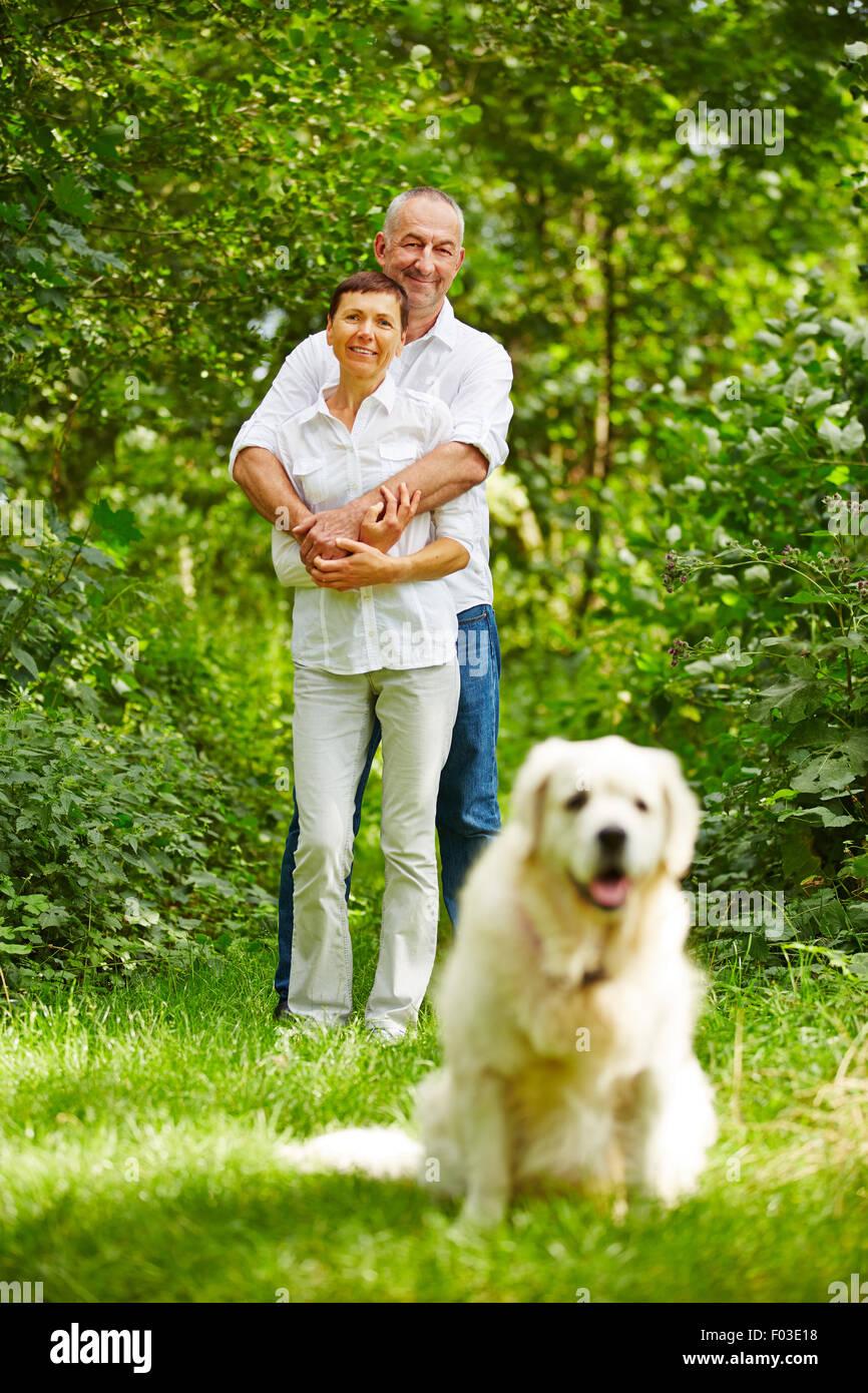 Coppia senior con il golden retriever cane come un animale domestico nel loro giardino Immagini Stock