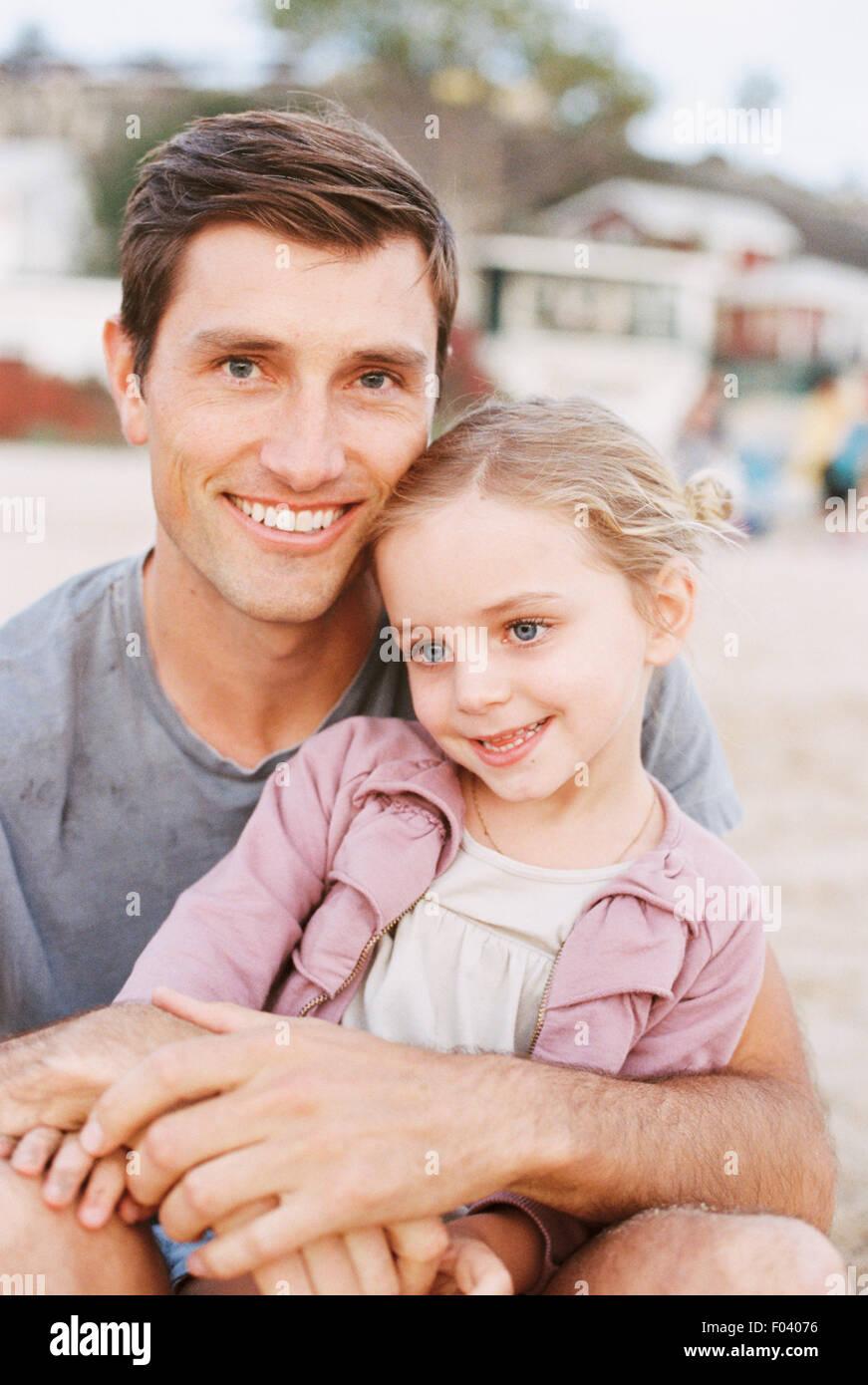 Giovane ragazza seduta sul suo padre il giro, guardando la telecamera, sorridente. Foto Stock