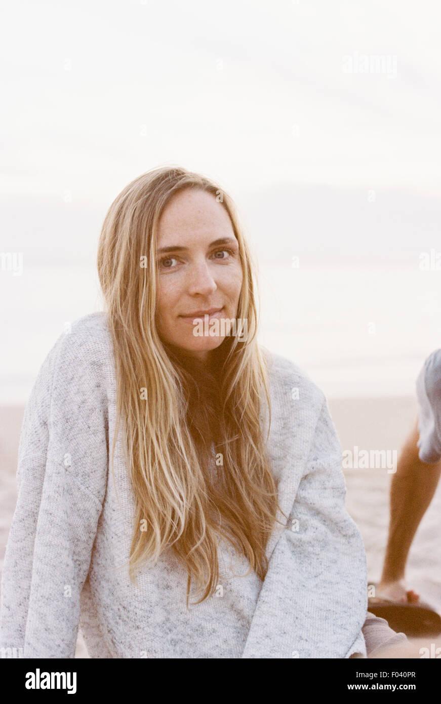 Donna seduta su di una spiaggia di sabbia in un ponticello, alla fine della giornata. Immagini Stock