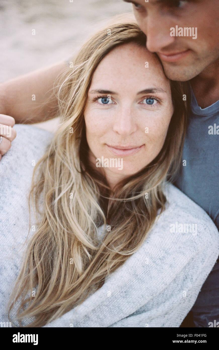 Una coppia di uomo e donna seduta su una spiaggia braccia attorno a ciascun altro, al tramonto. Immagini Stock