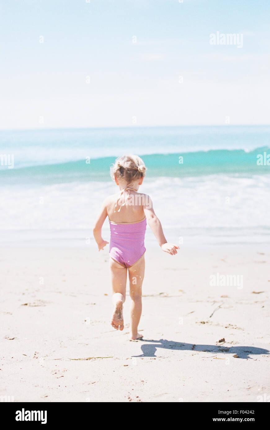 Giovane ragazza in un costume da bagno rosa in esecuzione su di una spiaggia di sabbia. Immagini Stock